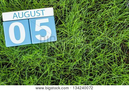 August 5th. Image of august 5 wooden color calendar on green grass lawn background. Summer day. Empty space for text.