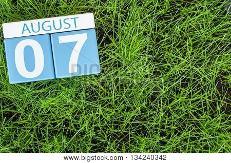 August 7th. Image of august 7 wooden color calendar on green grass lawn background. Summer day. Empty space for text.
