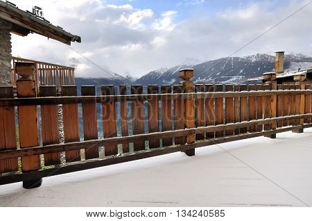 wooden railing of a terrace with snow - cottage in Savoie - France