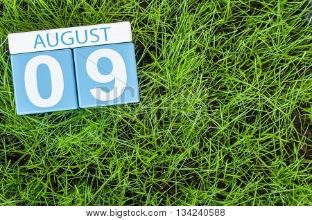 August 9th. Image of august 9 wooden color calendar on green grass lawn background. Summer day. Empty space for text.