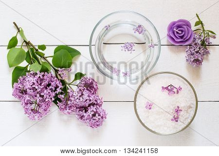 Flower SPA concept: bath with flower water sea salt aromatic candle and lilac flowers on white wooden table. Top view