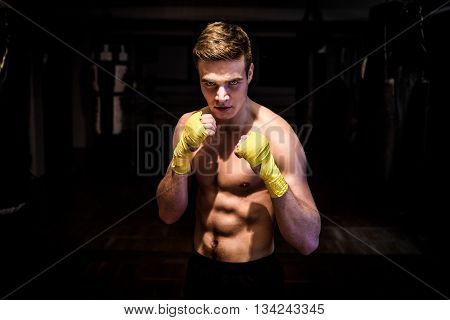 Street fighter mma boxer with bandages ready for fight club. Athletic ripped young man with big abs and wraps in a gym after a kickbox workout is looking at the camera.