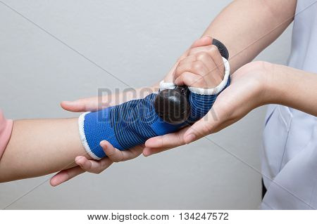 Physical therapist assisting patient woman in lifting dumbbellsrehabilitation concept