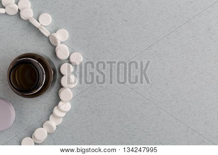 Brown glass pill bottle and round white pills.Top view