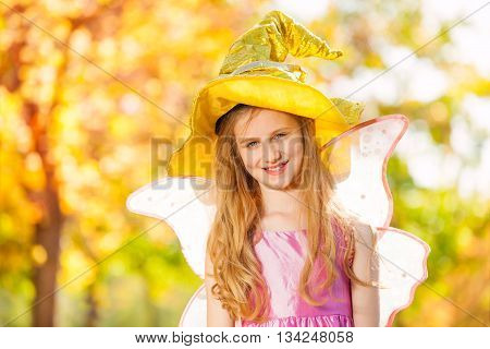 Girl in costume of fairy standing alone in the forest during sunny autumn day time
