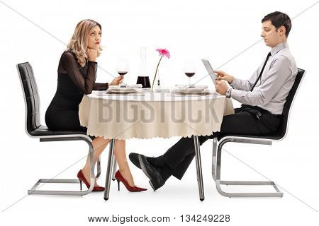 Bored woman sitting on a date with a man playing on a tablet isolated on white background