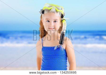 Happy little girl in blue swimsuit with diving mask on blurred sea background
