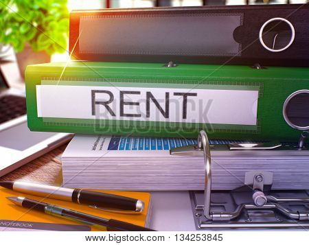 Rent - Green Office Folder on Background of Working Table with Stationery and Laptop. Rent Business Concept on Blurred Background. Rent Toned Image. 3D.