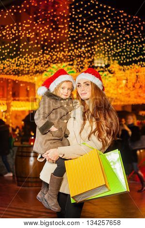 Young mother after holiday shopping holding her little daughter at her hands and wearing red Santa's hat with white pompon