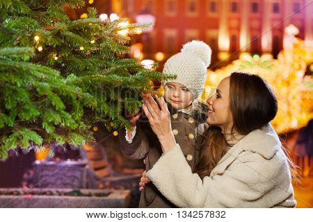 The smiling family of two people close to green Christmas tree at the evening square