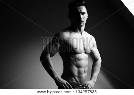 Sexy young man with muscular body and bare torso posing near window black and white