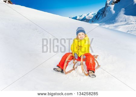 Little boy slide down the hill in the mountain on sledge