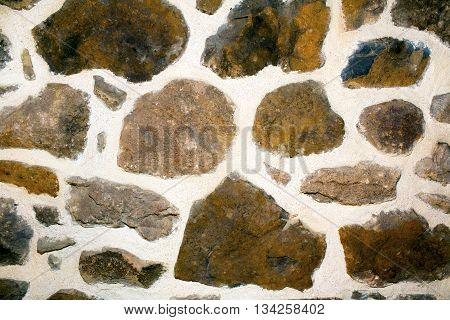 Stone wall texture with brown uneven sized rocks with large plastered areas