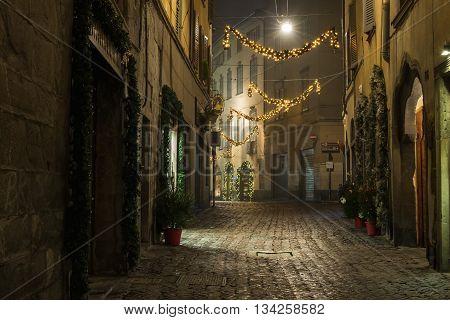 BERGAMO, ITALY - 12, JANUARY. Old European narrow empty street of medieval town with Christmas decoration on a foggy evening. Taken in Bergamo, Citta Alta, Lombardia, Italy, in January, 2016