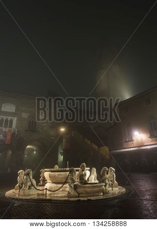 BERGAMO, ITALY - 12, JANUARY 2016.Central square of medieval town with fountain on a foggy evening. Taken on Piazza Veccia in Bergamo, Citta Alta, Lombardia, in winter, 2016