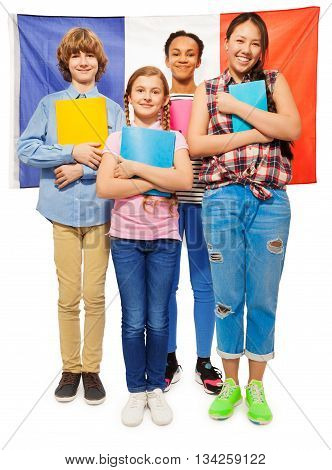 Whole-length picture of multi ethnic teenage students standing with textbooks against French flag, isolated on white