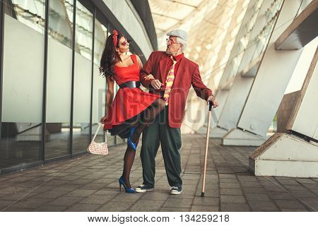 Old man dancing with a young girl they dressed in retro.