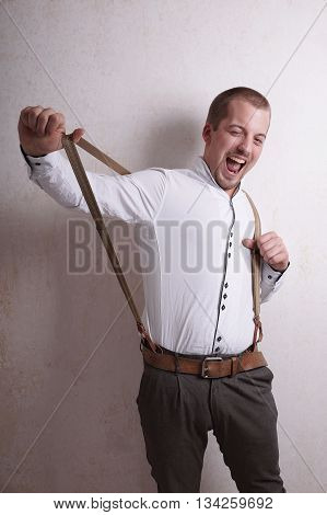 young man having fun with braces or suspenders