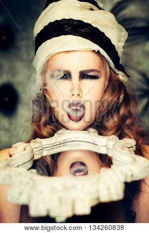Young fashionable woman with pretty face and bright makeup breathes smoke with stylish headdress and white mirror closeup