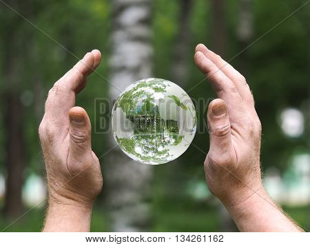 Workers hands dirty person. Glass ball floating in weightlessness. Background nature, green trees. Concepts, ideas