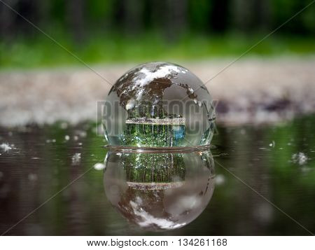 Transparent ball in the water on a forest background. The concept - ecology, environment, water Ballance