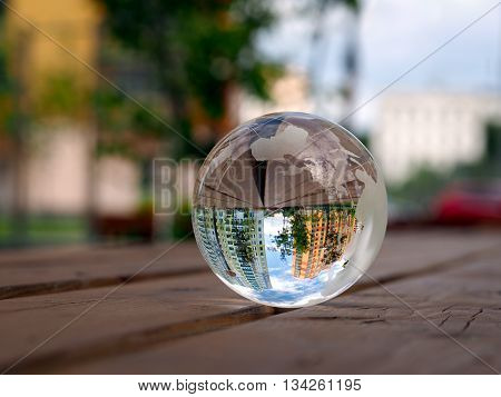 Beautiful new house buildings are reflected in a transparent bowl. Blue sky, clouds. Green trees. The ball lies on the wooden boards