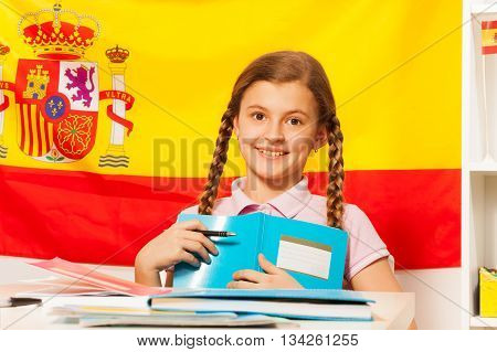 Cute teenage girl with two plaits, holding book, the flag of Spain behind her