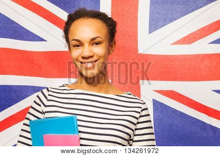 Close-up portrait of smiling African teenage student with textbooks, with flag of Great Britain on background