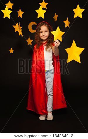 Full length picture of little girl in red cape with hood, holding big yellow paper star in her hand, standing against black background