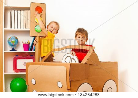Two 5 years old boys studying road rules with toy cardboard light and car