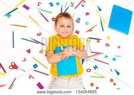Top view of kid boy holding textbook and laying among heap of stationery