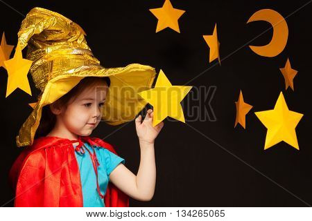 Beautiful five years old girl playing sky watcher with handmade stars and moon against black background