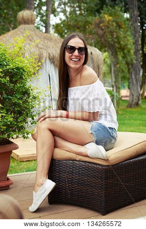 Portrait of attractive young woman in sunglasses sitting on a cushion and laughing in the garden on sunny day