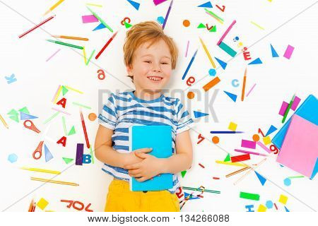 Top view of smiling five years old boy holding textbook and laying among the heap of colored school office supplies