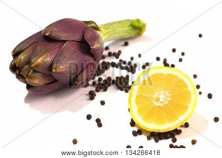 Ripe artichokes lemon and black pepper closeup on a white background. Isolated object.