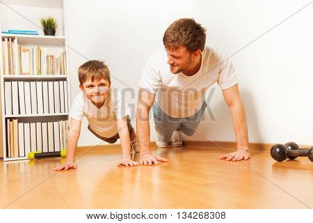 Father teaching his kid son doing push-ups exercises at the room floor
