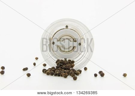 a pepper-mill with peppercorns on white background.