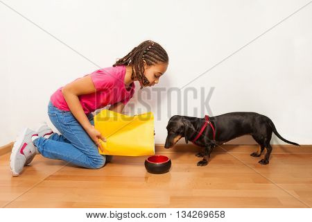 Black girl put food on dog plate on the floor at home