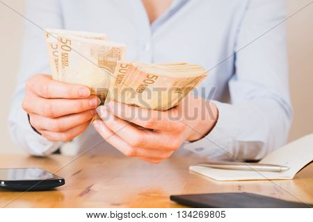 Woman counting money and calculating budget on a paper notebook.
