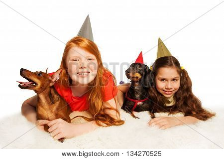 Smiling girls and their pets in birthday hats having fun on birthday party isolated on white