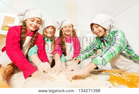 Four friends, kids in cook's uniform, kneading bakery dough in the kitchen