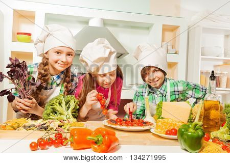 Three young cooks, girls and boy in uniform cutting traditional Italian pizza at the kitchen