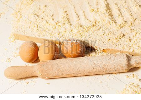 Three eggs and wooden rolling pin stained with flour