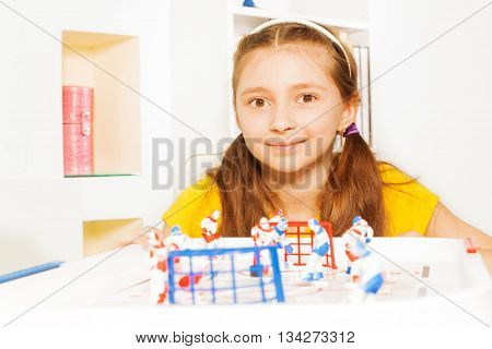 Beautiful ten years old girl playing indoors ice hockey table board game