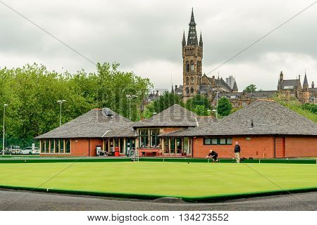 GLASGOW SCOTLAND - JUNE 13 2016: Two unidentified men playing bowls at the bowling greens at Kelvingrove in central Glasgow. Glasgow University in background.