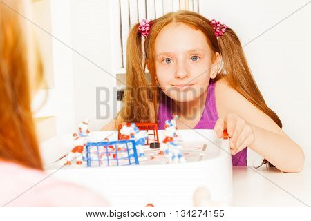 Cute girl with two pigtails playing indoors ice hockey table board game