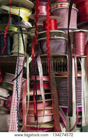 Piles of rolls of satin ribbing of different colors on wooden shelf