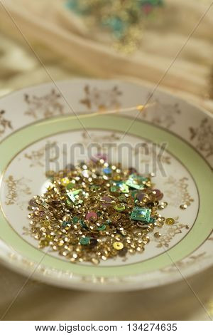 An assortment of gold and green sequins in ceramic bowl