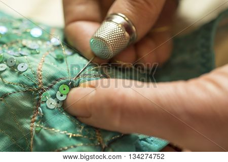 Hand with thimbled thumb pushing needle with gold thread through green garment