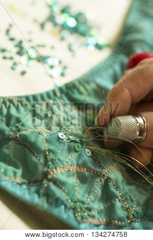 Fingers pulling gold thread through a green sequin on a green garment.
